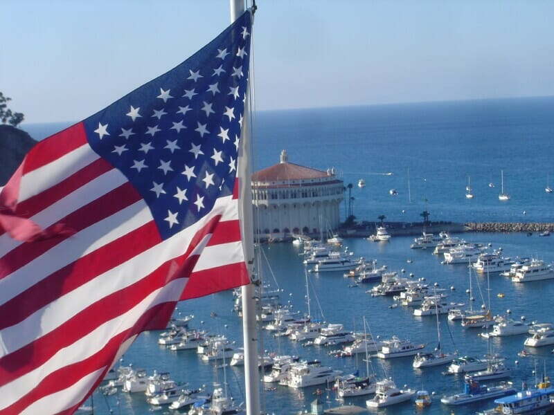 boats parked in a marina with an american flag in foreground