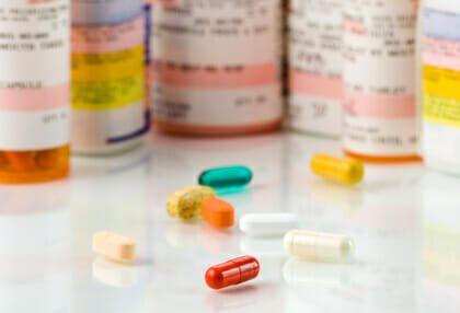 several bottles of prescription pills and single pills on table