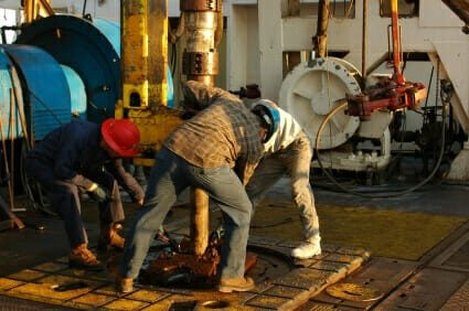 three workers tending to an oil extraction rig