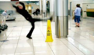 Person in shopping center slipping and falling next to a caution wet floor sign