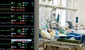 Patients in hospital bed with vital sign monitor in foreground.