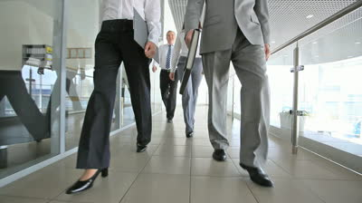 stock-footage-team-of-four-walking-along-the-corridor-of-the-office-building