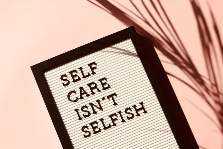 A framed picture with the words 'self care isn't selfish' written across the middle. There is a plant in the foreground.