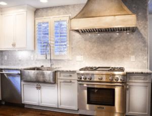 Kitchen with Thompson Traders farmhouse sink and custom rangehood