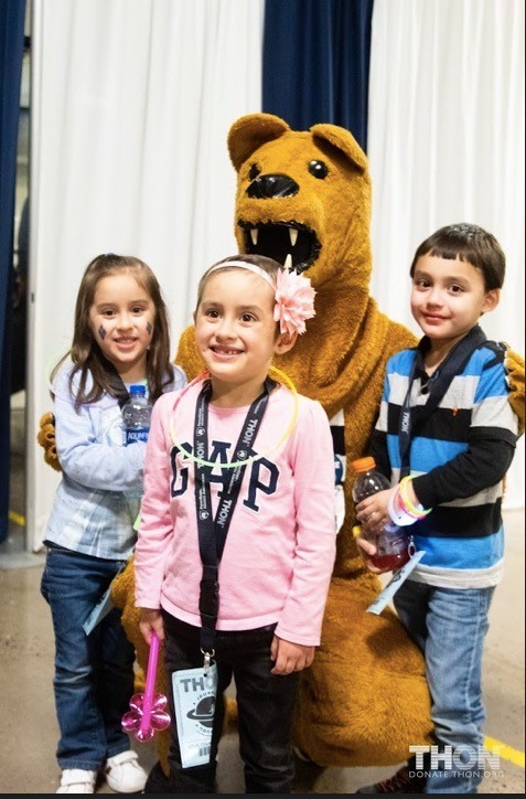 A group of children posing with a mascot  Description automatically generated with medium confidence