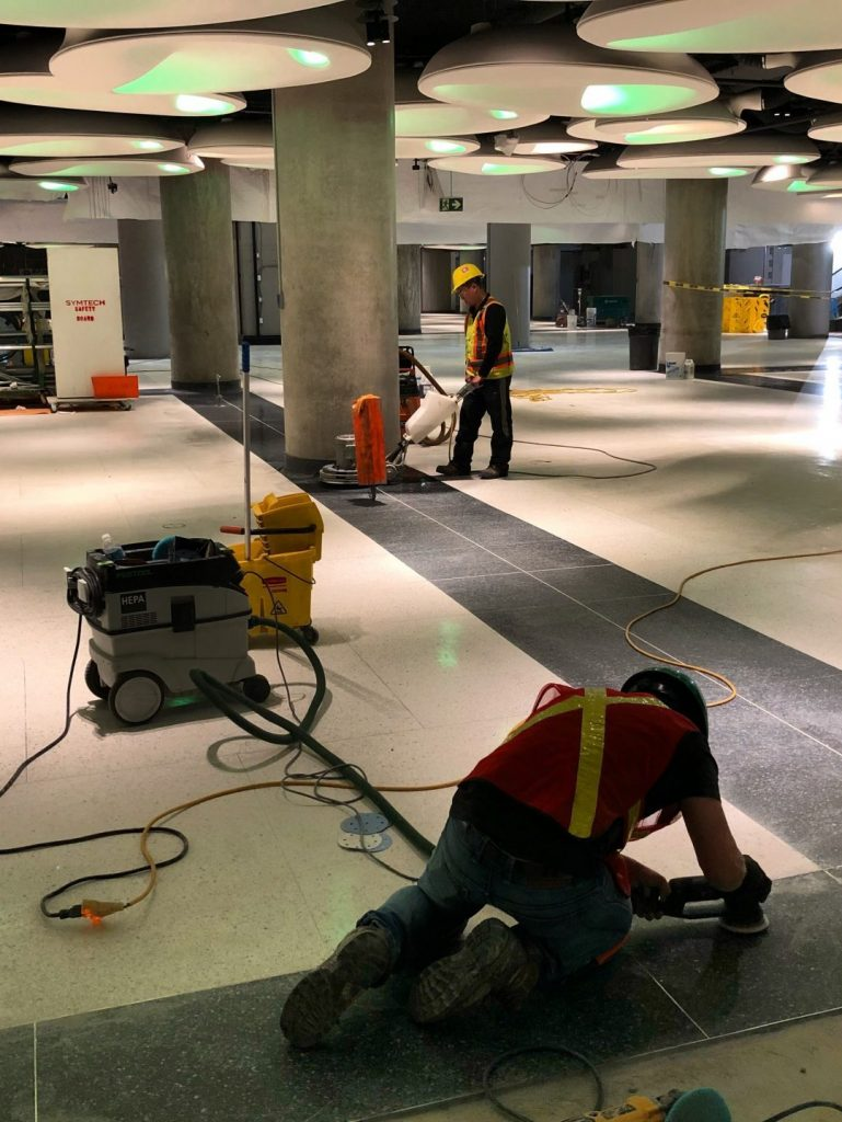Thor & Partners restoration work on a marble floor of a building two people are restoring the floor