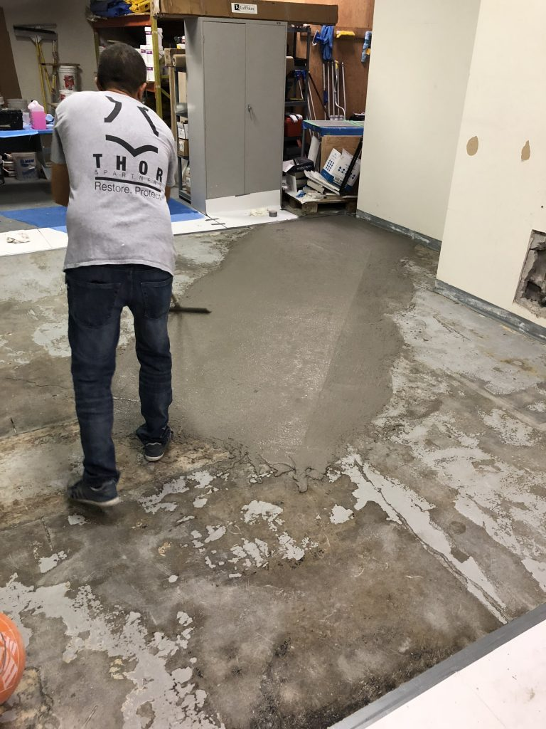 Thor and Partners . Concrete . CEMENTITIOUS OVERLAY SYSTEM, an employee of Thor & Partners is working on concrete floor