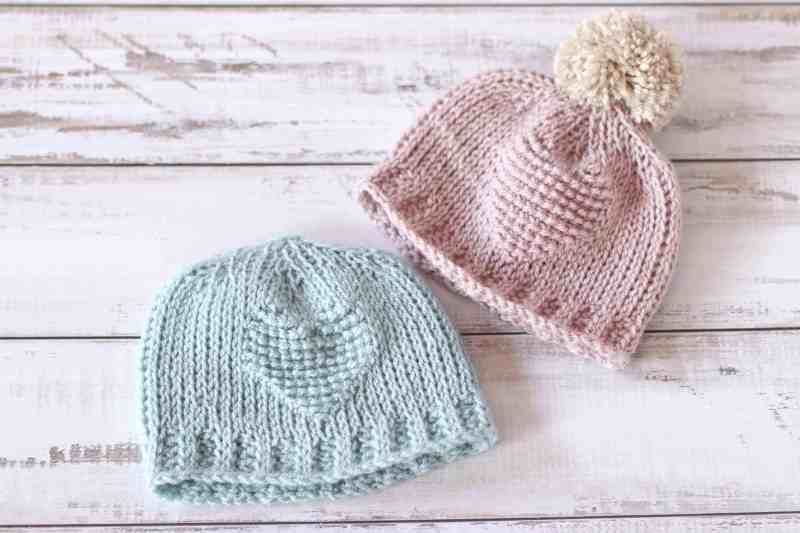 Two Tunisian crochet baby hats in pink and mint green, with heart embellishment.