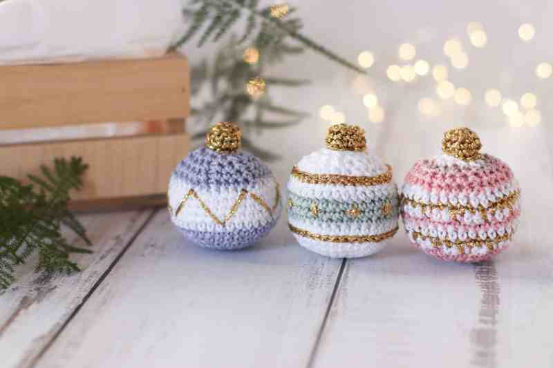 three crocheted Christmas baubles in pastels and gold