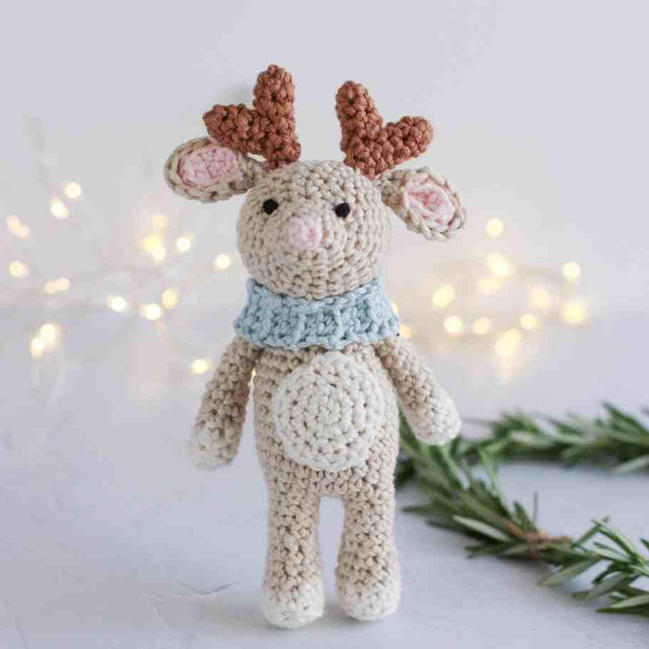 crochet reindeer wearing a scarf with sparkly lights in the background