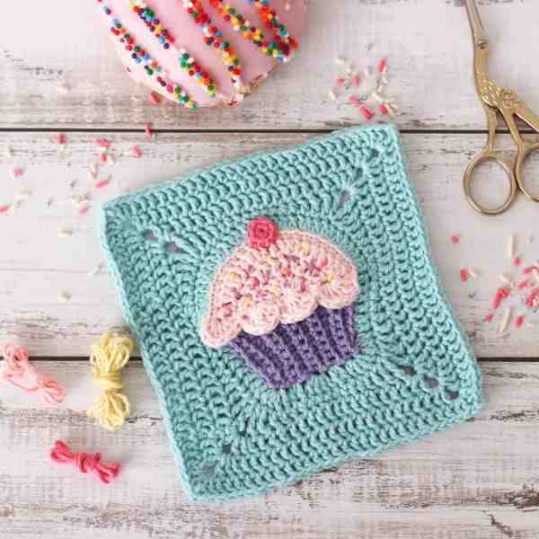 pink crochet cupcake square with a blue background, surrounded by sprinkles, yarn and donuts.