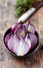 red-onion-halved-cut-in-half-in-a-bowl-metal-wooden-counter-top-surface-purple-colours-healthy-eating-clean