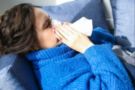 woman-lying-blowing-nose-allergy-free-home