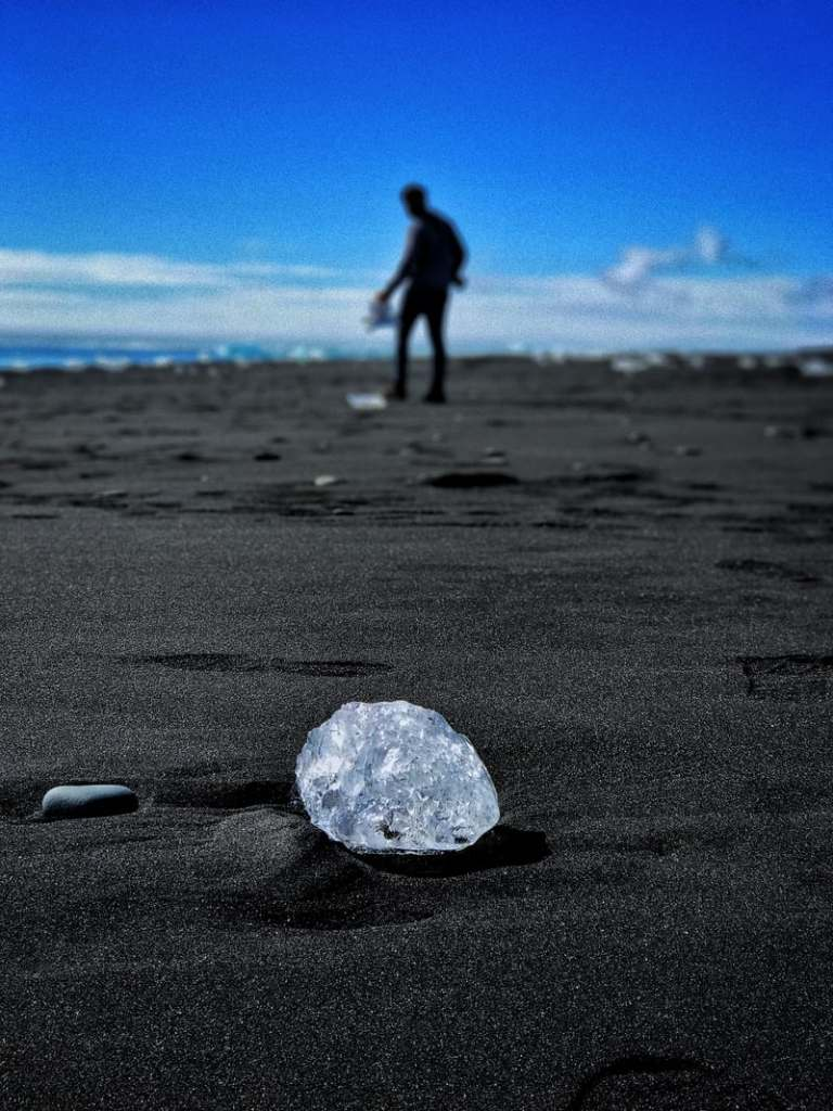 An uncut diamond laying on the beach with a person in the background.