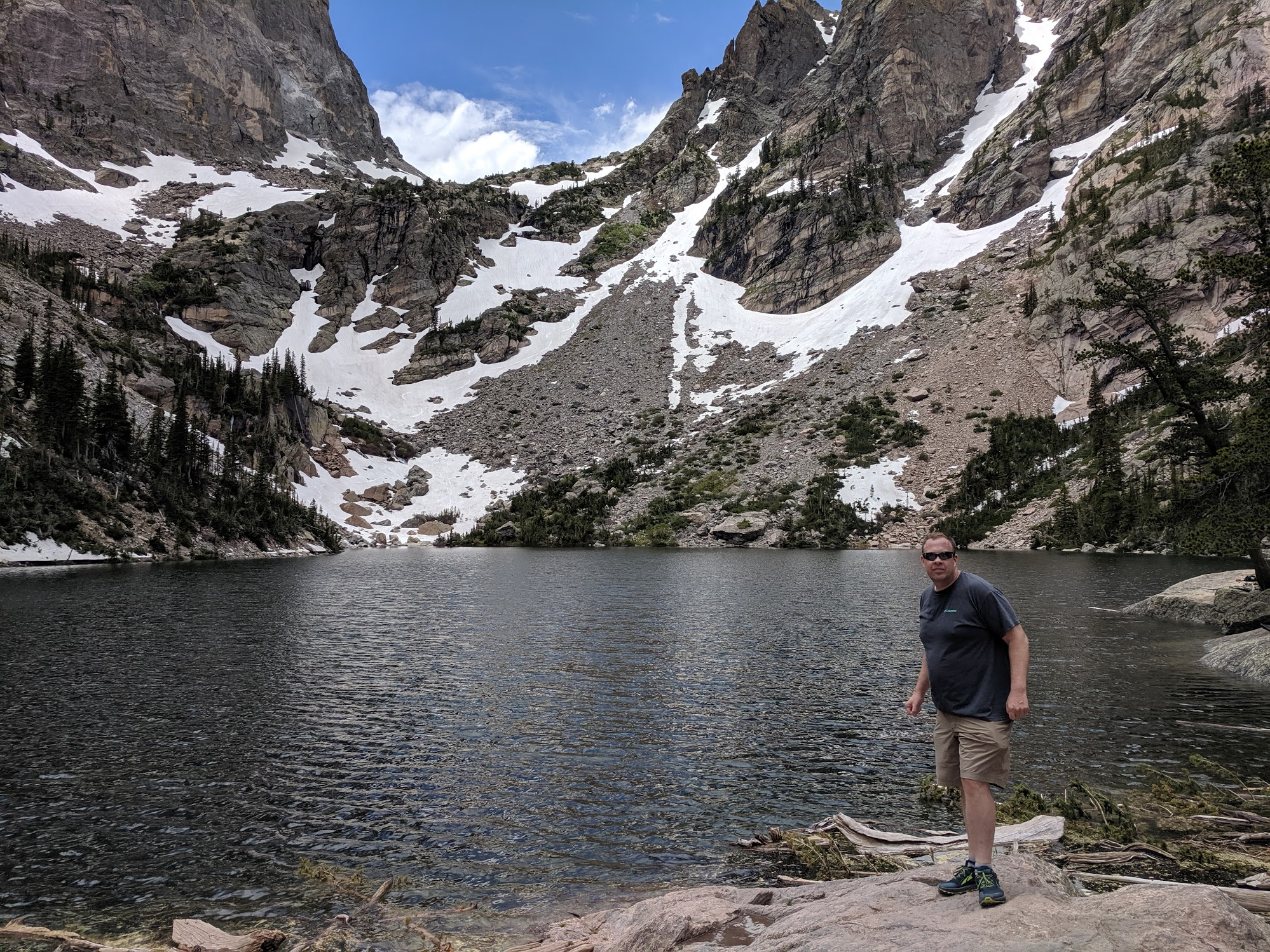 ThosPFuller on a hike in Colorado with a lake in the foreground and mountains in the background.