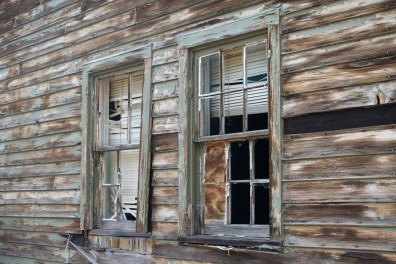 Windows of an abandoned cabin near the trailhead