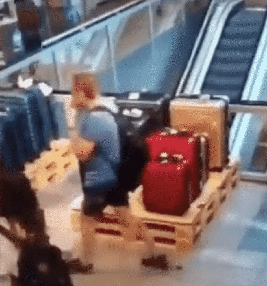 man casually shits on the floor while walking through airport, another man slips and falls in it