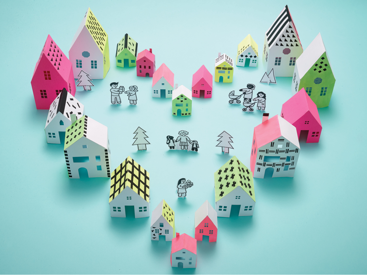 Small model houses made out of paper in a heart shape surrounding families made out of paper