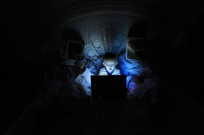 Boy looking at computer screen in the dark