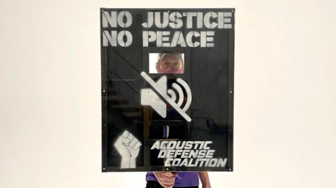 Sign with hole cut out saying 'NO JUSTICE NO PEACE'