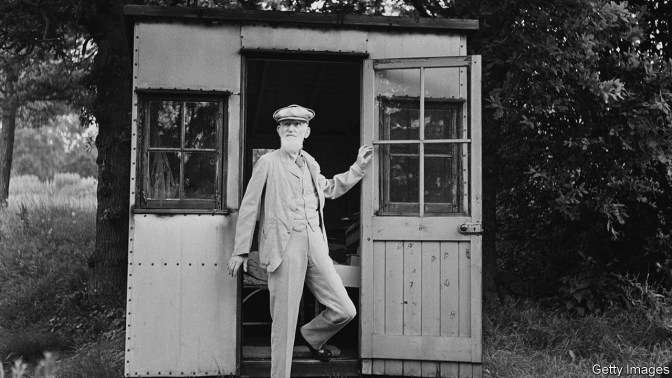 Black-and-white photo of a man with beard emerging from shed