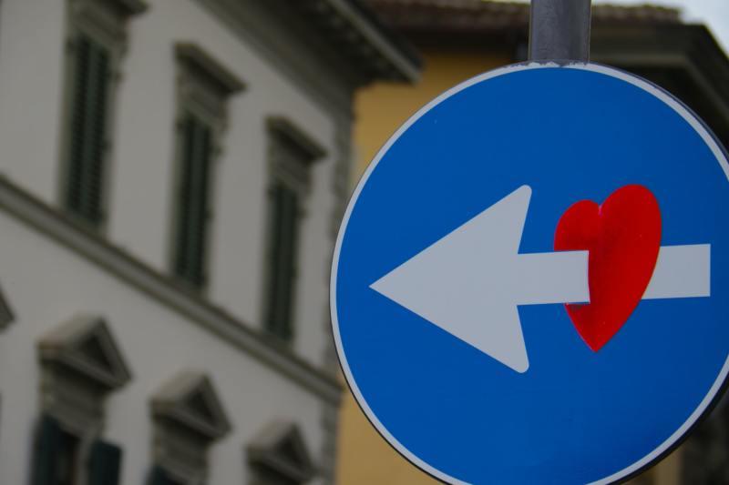 Street sign arrow going through a red heart