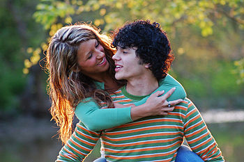 English: A young woman and man embracing while...