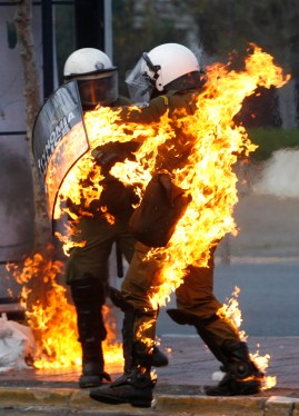 A riot policeman covered in flames runs to escape during in riot in Athens