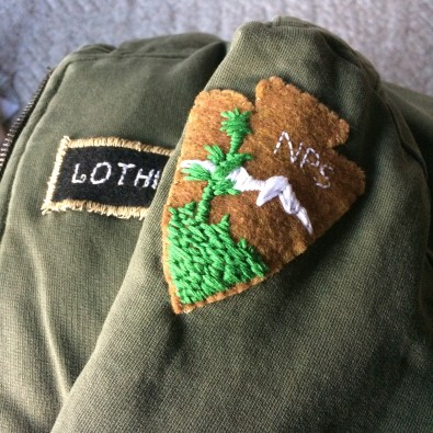 A closeup of the patches I made, I made him a name plate using the very basic embroidery font my sewing machine can do then I stitched over it to thicken it up. I did his National Park Service patch by hand while checking an image I had saved onto my ipad, that embroidery book really paid off. I hand stitched both patches to the coat, this became his fall coat, the patches are still there.