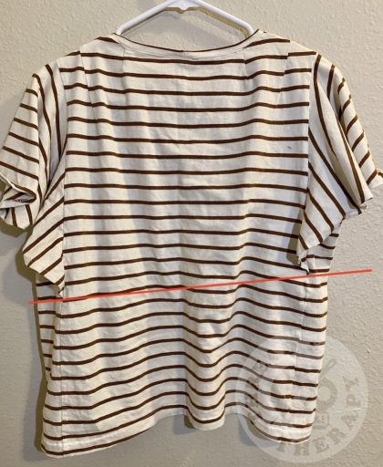The back side of a finished Style Arc Posie Knit top on a hanger. A red line illustrates that one sleeve flounced has stretched longer than the one on the right.