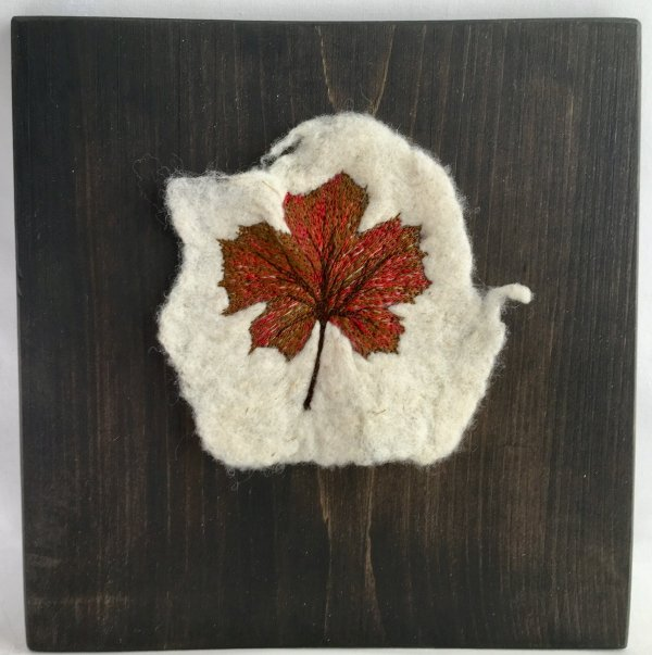 Felted fabric with embroidered fall maple leaf mounted on a pine bard and stained with natural walnut stain