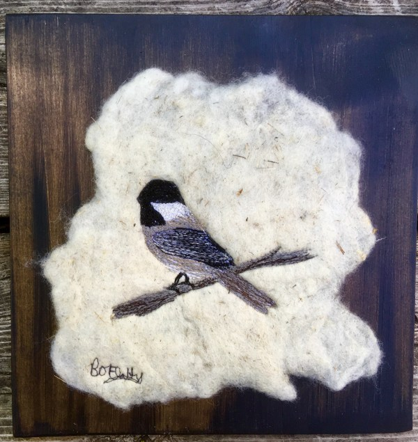 Chickadee embroidered on wet felted local wool and mounted on pine board