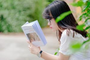 Girl reading a book to get better comprehension with self-questioning.