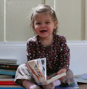 Smiling female toddler with a book in her lap.