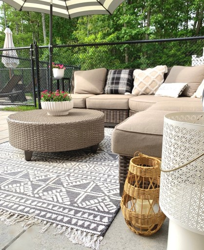 patio area with c shaped couch, patio table, lanterns and woven rug