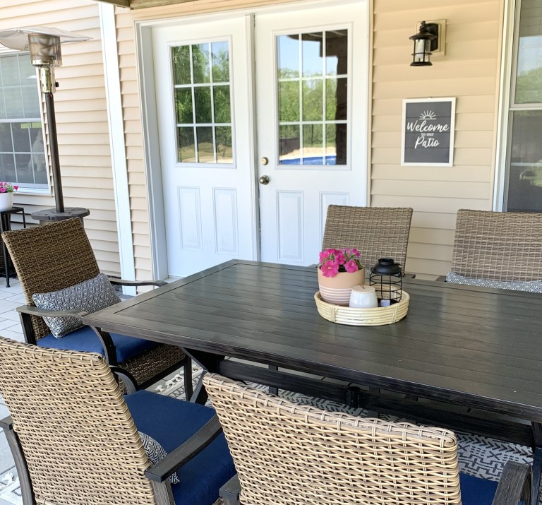 patio dining table decorated with a tray of pink flowers, lantern, and candle with diy wood stenciled patio sign in the background