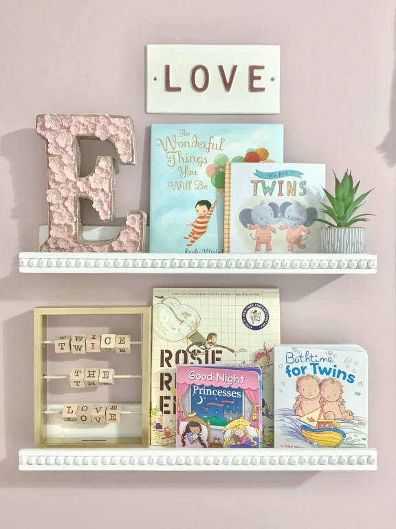 tiered wood bookshelves with assorted nursery books and handmade abacus sign