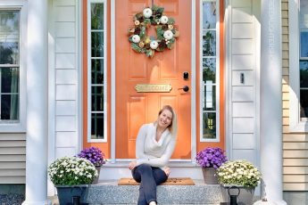 festive fall entry with a bright orange door, pumpkins, lanterns, and assorted fall florals