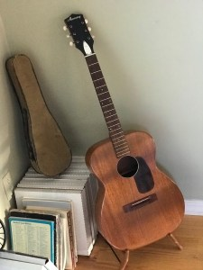 Guitar without strings leaning in a corner