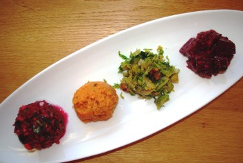 Jeweled palette of sides (Cranberry Relish, Mashed Sweet Potatoes with Chipotle, Carmelized Brussels Sprouts with Pecans, Marinated Beets wtih Horseradish