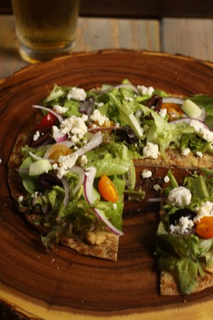 Mediterranean Flatbread with Grecian salad, on both our catering and restaurant menus.