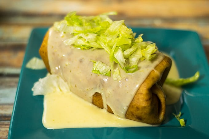 Beef and Bean Chimichangas topped with a delicious queso sauce!