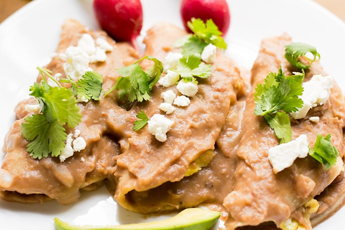 These breakfast enfrijoladas are so easy to make. They're corn tortillas covered in a delicious bean sauce and filled with scrambled eggs. Enjoy this yummy Mexican breakfast!