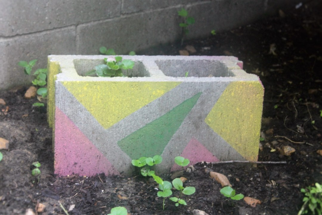grey cinder block spray painted with green and yellow triangles
