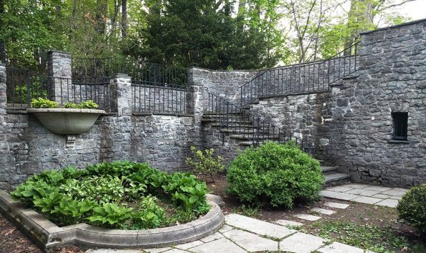 Stone steps lead visitors into a sunken garden behind the house.