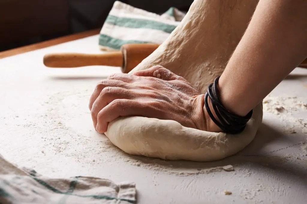 Руки замешивая тесто хлеба
