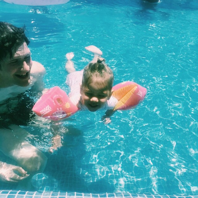 a toddler and father swimming in a pool