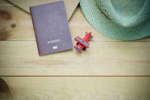 flatlay of passport, hat and a toy