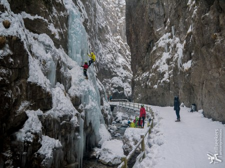 Ice climbing in Serrai di Sottoguda and tourist onlookers.