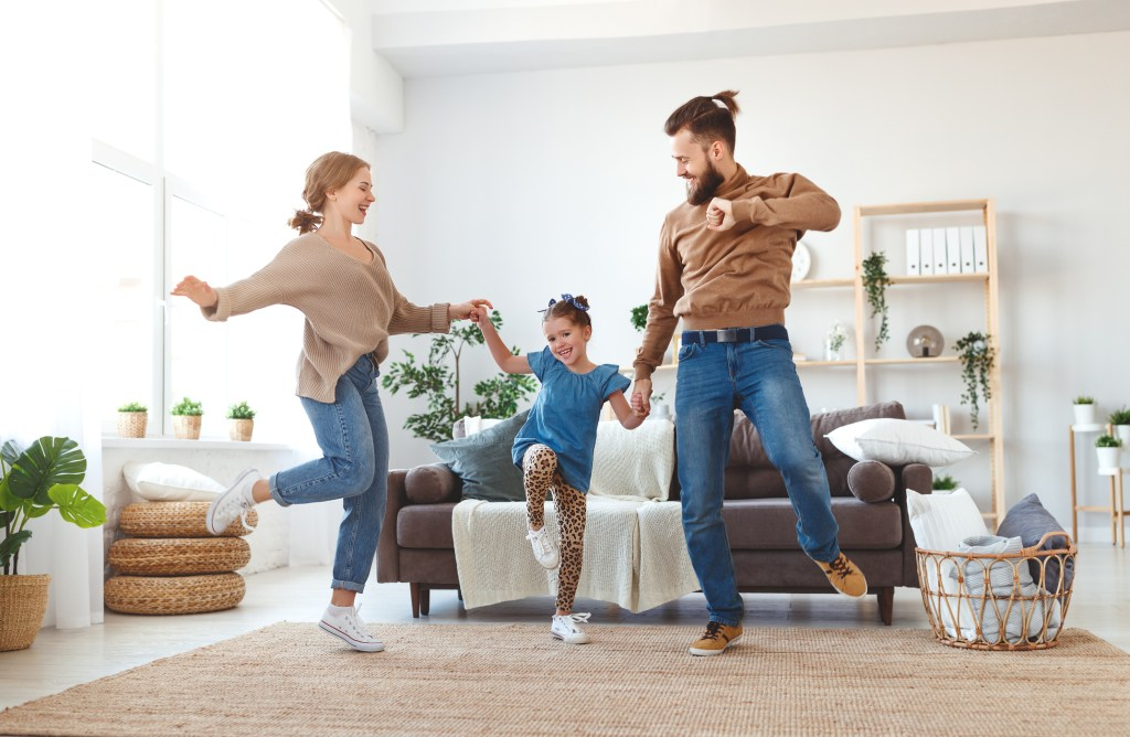 happy mum and dad dancing with daughter in living room